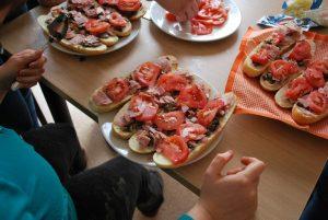 Ustawione na drewnianym stole talerze z kanapkami, obłożonymi wędliną i pomidorami.