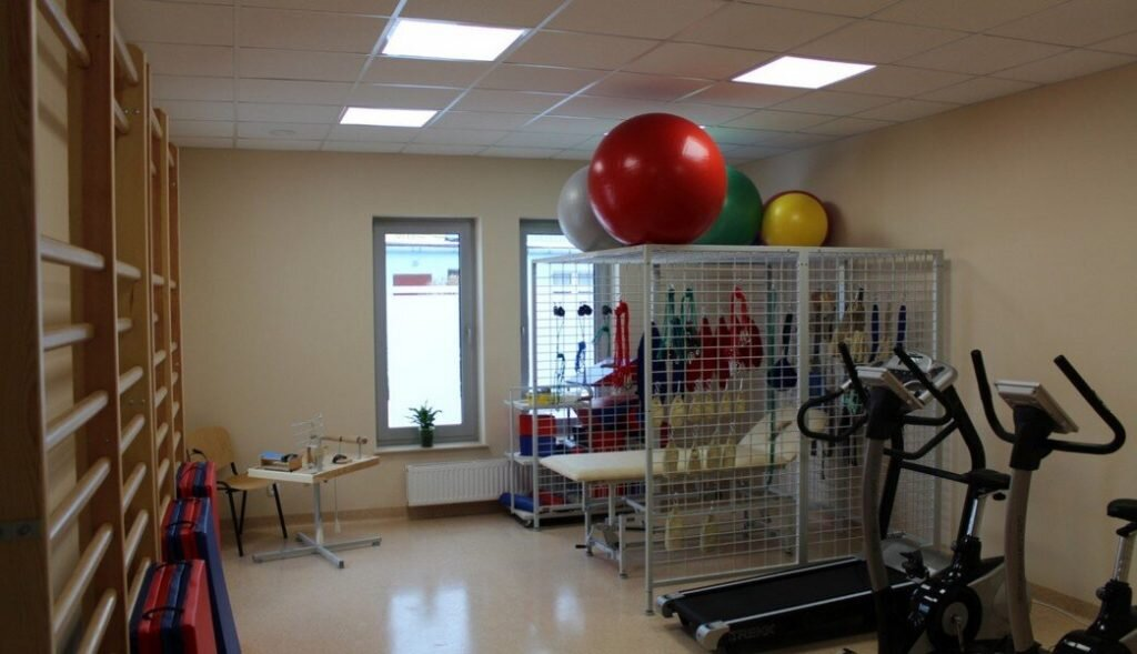 Sala rehabilitacyjna wyposażona w sprzęt do ćwiczeń, piłki gimnastyczne, bieżnie elektryczne, rowery treningowe, ławki do ćwiczeń.